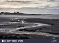 a-stream-meanders-through-mudflats-at-low-tide-in-morecambe-bay-with-the-seafront-of-sandyland...jpg